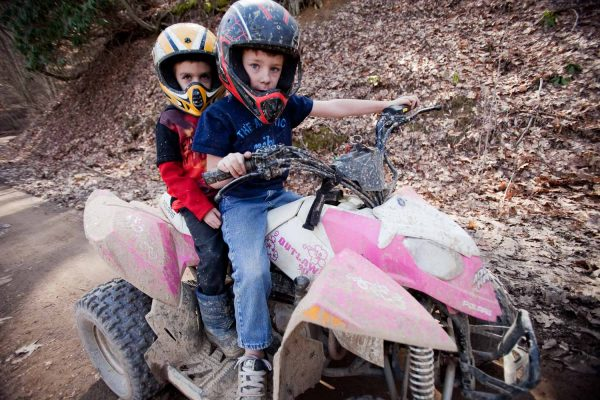 Two boys ride their pink Outlaw ATV with their father near Valley Falls State Park.
