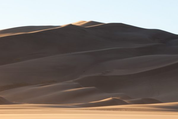 There is a person standing on the lower dune near the center, to give a sense of scale. The dunes are fuzzy not because of a lack of focus, but because there is a layer of sand blasting over the ridges in the wind.