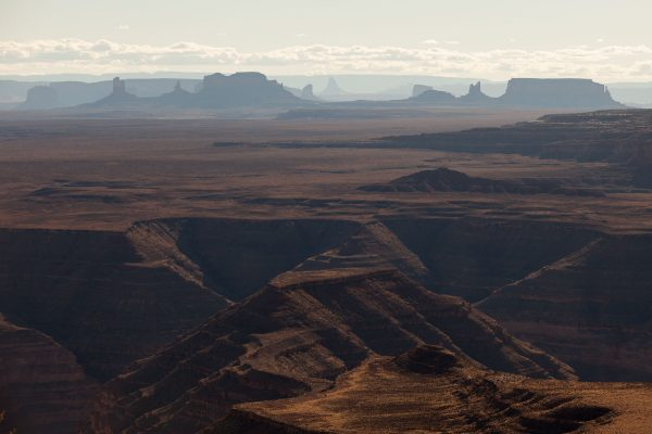 View from Muley Point: The San Juan River meanders deep out of sight through the Goosenecks area (foreground) while the buttes and mesas of Monument Valley rise in the distance.