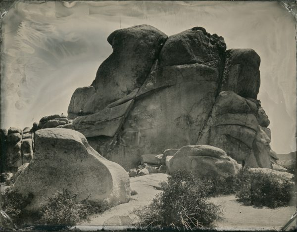 Joshua Tree National Park, California. If you look closely there are some people rock climbing on the left side of the outcrop.