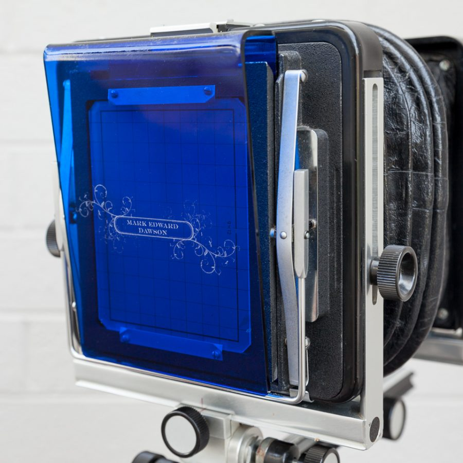 Groundglass cover with my name and a design etched into blue acrylic, shown here on my Arca-Swiss 4x5 camera.